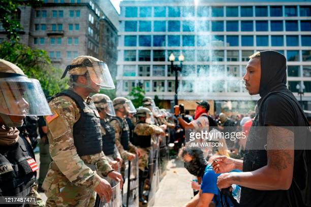A protester blows smoke into the faces of Army National Guard members as he and others demonstrate the death of George Floyd near the White House on...