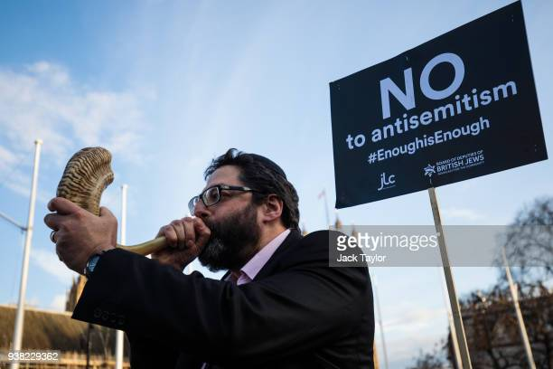 A protester blows through a shofar during a demonstration in Parliament Square against antiSemitism in the Labour Party on March 26 2018 in London...