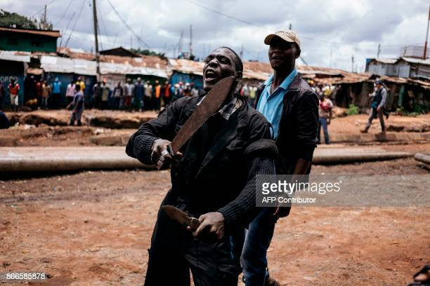A protester brandishes a machete and a knife during clashes with police forces in Kibera Nairobi on October 26 2017 Kenyans trickled into polling...