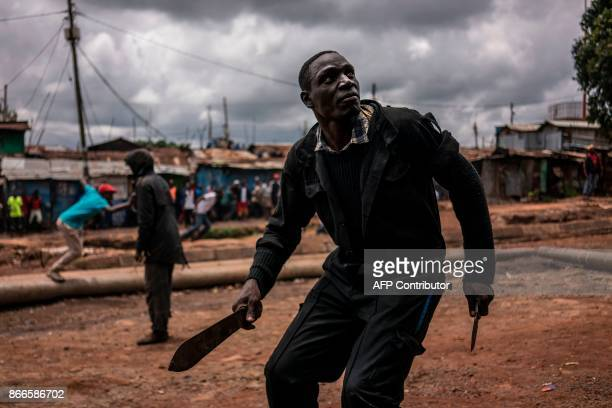 TOPSHOT A protester brandishing a machete and a knife prepares to take cover from incoming tear gas canisters during clashes with police forces in...
