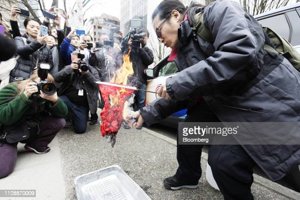 A protester burns a Chinese flag in front of the Supreme Court following a hearing of Huawei Technologies Co Chief Financial Officer Meng Wanzhou in...