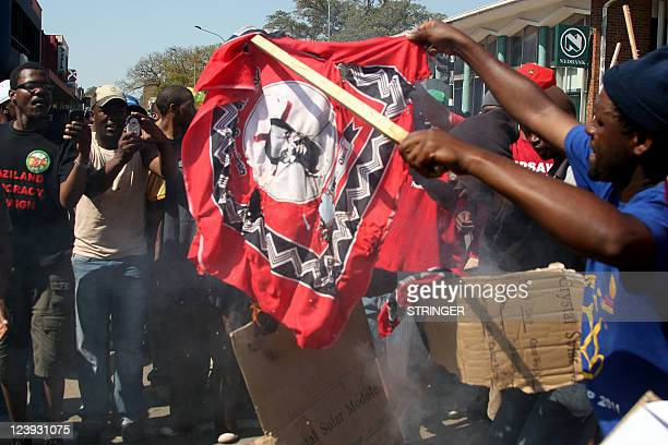 Protester burns a cloth with an image of King Mswati III during one of the largest protests yet against Africa's last absolute monarch and his...