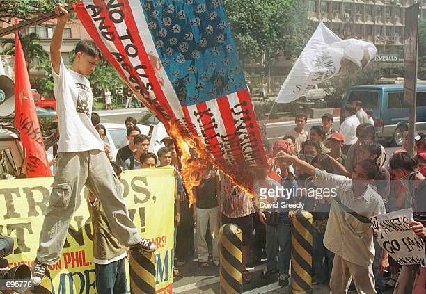 A protester burns a makeshift American flag during a demonstration outside the US Embassy January 30 2002 in Manila Philippines Several groups...