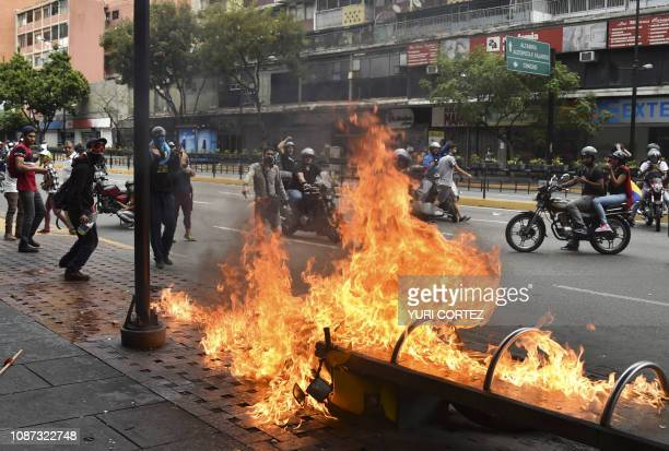A protester burns a motorcycle during clashes with the security forces in a protest against the government of President Nicolas Maduro on the...