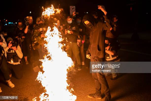 Protester burns an American flag on September 26, 2020 in Portland, Oregon. Oregon Governor Kate Brown declared a state of emergency prior to...