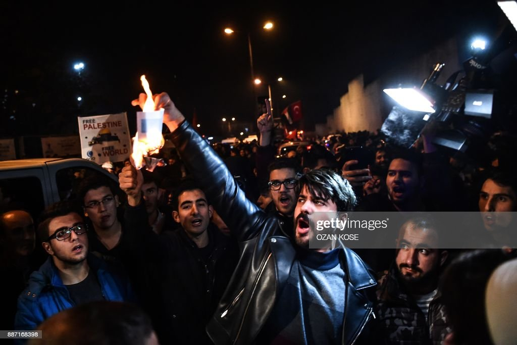 A protester burns an Israeli flag printed on a piece of paper during a demonstration against the US and Israel in front of the US consulate in Istanbul on December 6, 2017. Hundreds of people staged a protest outside the US consulate in Istanbul angrily denouncing the US president's move to recognise Jerusalem as the capital of Israel. Around 1,500 people gathered outside the well-protected compound close to the Bosphorus which was sealed off by police with barricades, an AFP correspondent said. /