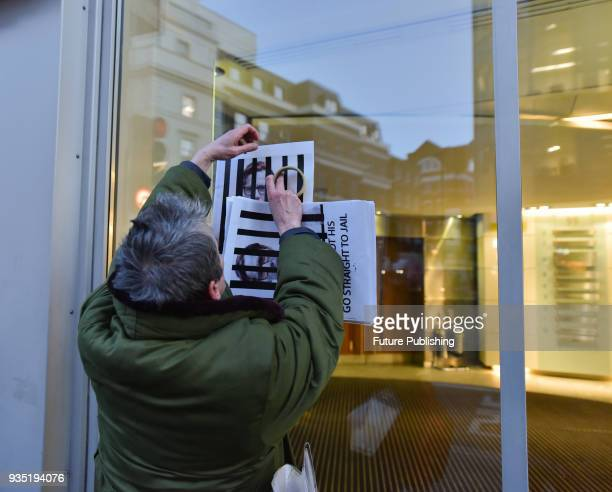 A protester called Heiko Khoo sticks posters of Alexander Nix behind bars onto the windows of the offices in a demonstration against Cambridge...