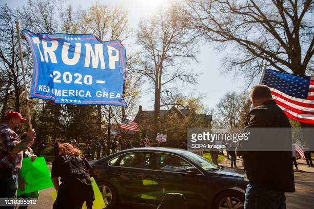 Protester campaigns for Trump while simultaneously protesting against the GOP governor of Indiana. Protesters gather outside Indiana Governor Eric...