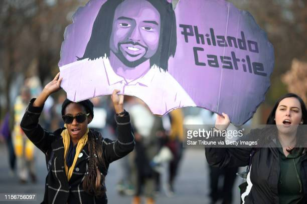 Protester carried a portrait of Philando Castile as family members and community activists marched to the location on Plymouth Ave where Jamar Clark...
