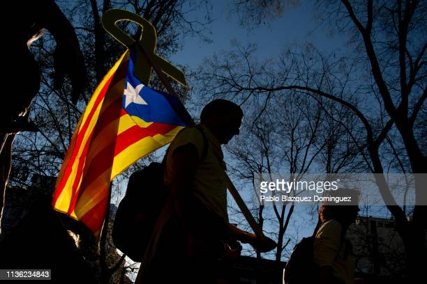 Protester carries a Catalan Independence flag and a yellow ribbon during a demonstration titled 'Self-determination is not a crime' on March 16, 2019...