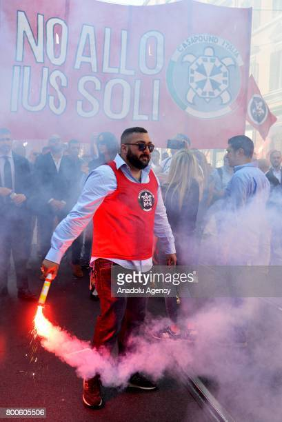 A protester carries a flare during a protest against the law on Jus Soli which would give birthright citizenships to children born to refugees living...