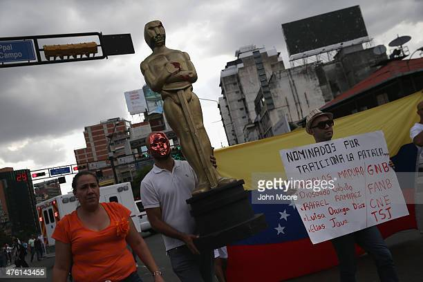 A protester carries a giant Oscar statue during an antigovernment demonstration on March 2 2014 in Caracas Venezuela Venezuela has one of the highest...