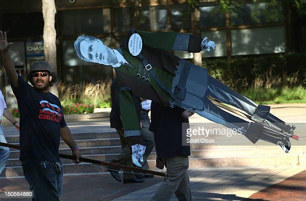 A protester carries a Mitt Romney puppet as he leaves a demonstration outside the offices of Bain Capital on August 21 2012 in Evanston Illinois The...