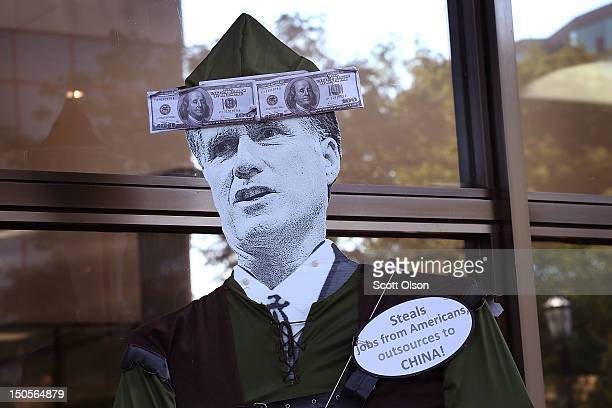 A protester carries a Mitt Romney puppet during a demonstration outside the offices of Bain Capital on August 21 2012 in Evanston Illinois The...