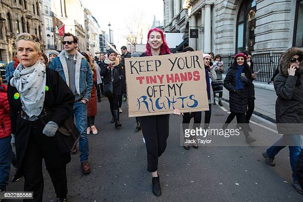 A protester carries a placard as they march from The US Embassy in Grosvenor Square towards Trafalgar Square during the Women's March on January 21...
