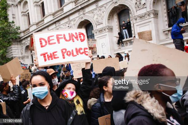 Protester carries a placard supporting calls to 'defund the police' as Black Lives Matter activists, gathered for the second consecutive day of mass...