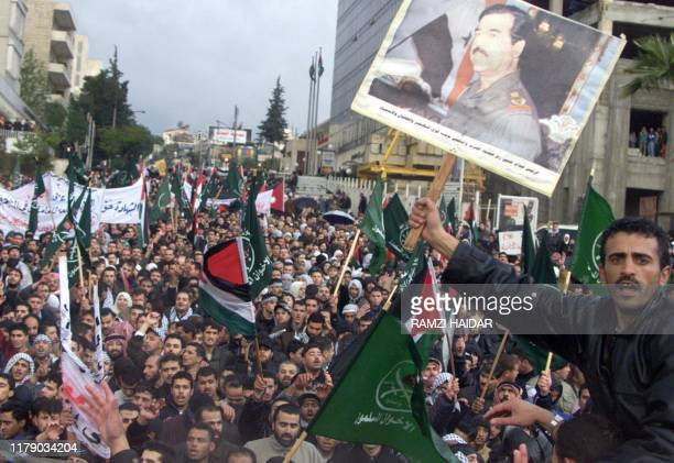 A protester carries a portrait of Iraqi President Saddam Hussein at a massive proPalestinian demonstration 02 April 2002 in Amman which organizers...