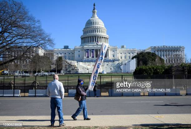 Protester carries a sign calling for Congress to impeach US President Donald Trump, near the US Capital in Washington, DC on January 10, 2021. -...