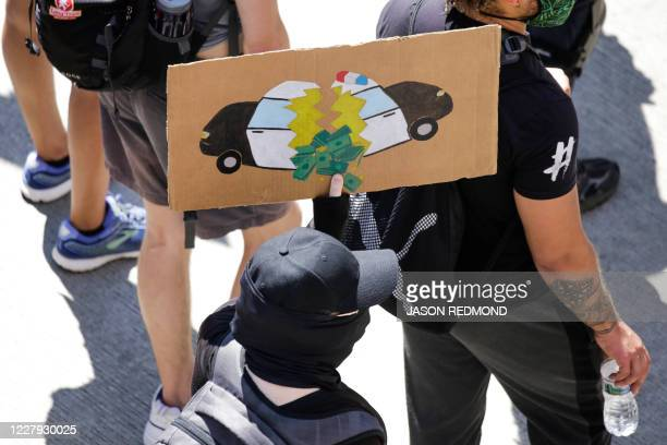"""Protester carries a sign during a """"Defund the Police"""" march from King County Youth Jail to City Hall in Seattle, Washington on August 5, 2020."""