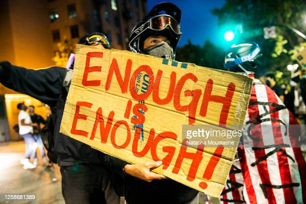 Protester carries a sign during a march on July 25, 2020 in Oakland, California. Demonstrators in Oakland gathered to protest in solidarity with...