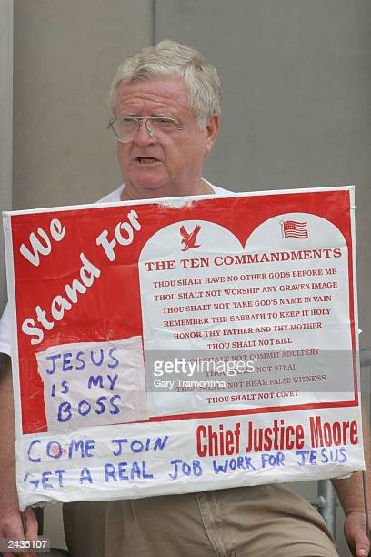 A protester carries a sign outside the state judicial building where workers earlier carted away the 2 1/2 ton Ten Commandments monument at the...