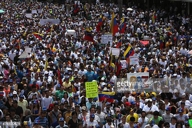 A protester carries a sign reading Peace as thousands of protesters march in a massive antigovernment demonstration on March 2 2014 in Caracas...