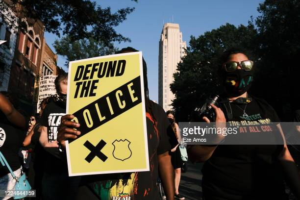 A protester carries a sign that reads Defund The Police during the Black Women Matter Say Her Name march on July 3 2020 in Richmond Virginia Protests...