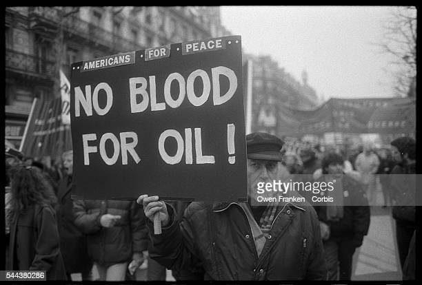 A protester carries a sign with crowds of Parisians marching in the streets of Paris against the Gulf War