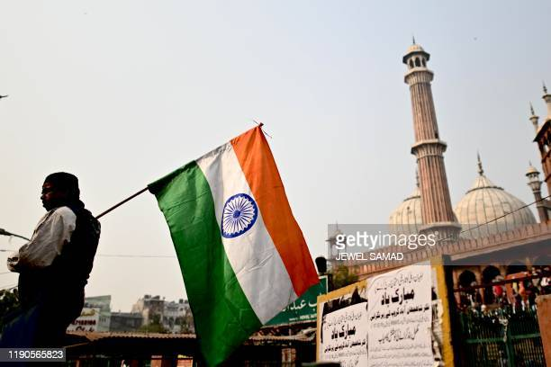 A protester carries an Indian national flag outside the Jama Masjid mosque during a demonstration against India's new citizenship law in the old...