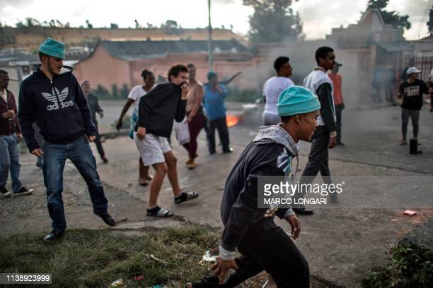 A protester carries stones in the street of Johannesburg on April 23 2019 during a protest against the lack of service delivery or basic necessities...