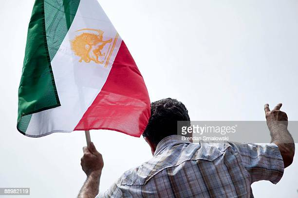 A protester carries the Iranian flag during a rally July 11 2009 in Washington DC Activists gathered to rally for the current uprising in Iran over...