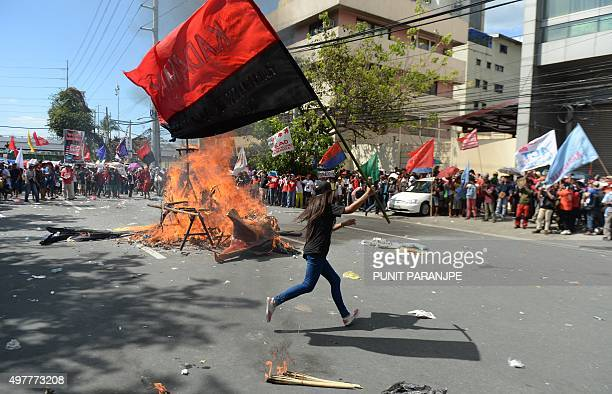 Protester carrying a flag from a local organisation runs past a fire after an effigy of an American eagle was set alight during a demonstration...