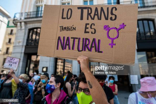 Protester carrying placard reading 'Trans is also natural' during a demonstration against transphobia.The Spanish Congress will approve a bill that...