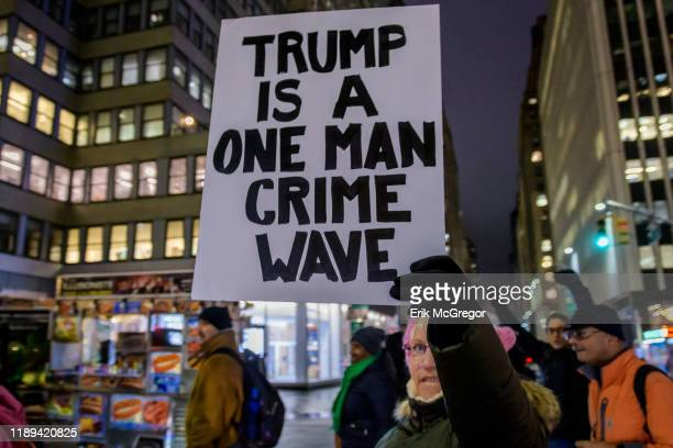 Protester carrying signs and marching down Broadway The night before the House of Representatives takes a somber vote to impeach Trump hundreds of...
