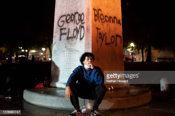 A protester catches his breath under the names of George Floyd and Breonna Taylor on September 23 2020 in Portland United States Violent protests...
