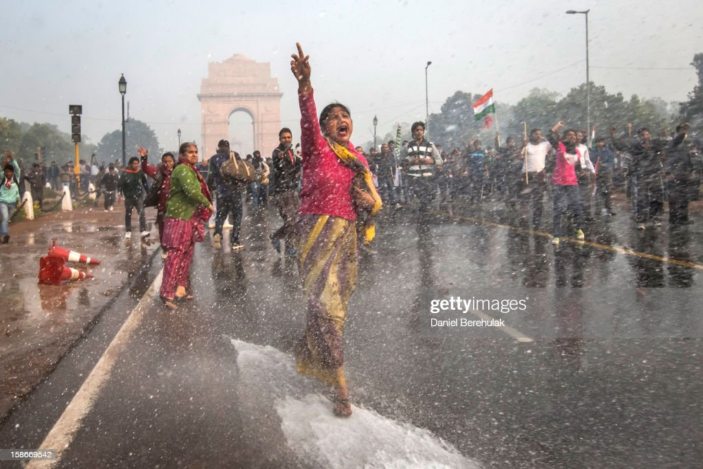 A protester chants slogans as she braces herself against the spray fired from police water canons during a protest against the Indian government's reaction to recent rape incidents in India, in front of India Gate on December 23, 2012 in New Delhi, India. The gang rape of a 23-year-old paramedical student on a moving bus on December 16, in Delhi, has led to people to react openly against the government's current rape laws. Over a thousand protesters gathered in front of Delhi to protest against lax laws and the government's handling of recent rape cases all over India.