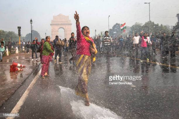 A protester chants slogans as she braces herself against the spray fired from police water canons during a protest against the Indian government's...