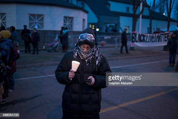 A protester checks their phone at a candlelight vigil held for Jamar Clark outside the 4th police precinct November 20 2015 in Minneapolis Minnesota...