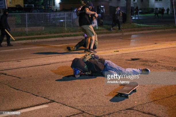 Protester clashes with armed civilian Kyle Rittenhouse as another man lies on the ground having been shot in the chest during confrontations between...