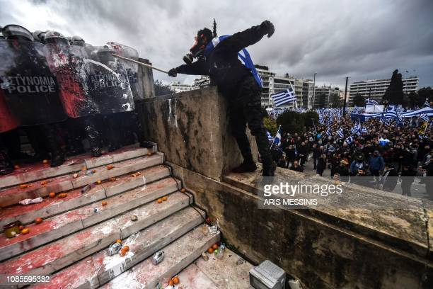 TOPSHOT A protester clashes with riot police in front of the Greek Parliament in Athens on January 20 2019 during a demonstration against the...