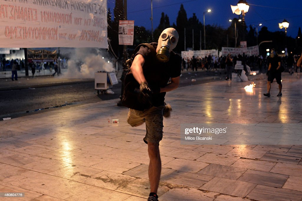 A protester clashes with riot police in front of the Greek Parliament on July 15, 2015 in Athens, Greece. Anti-austerity protesters hurled petrol bombs at police in front of Greece's parliament as lawmakers began debating deeply unpopular reforms needed to unlock a new eurozone bailout. Riot police responded with tear gas against dozens of hooded protesters who set ablaze parts of Syntagma square in central Athens.