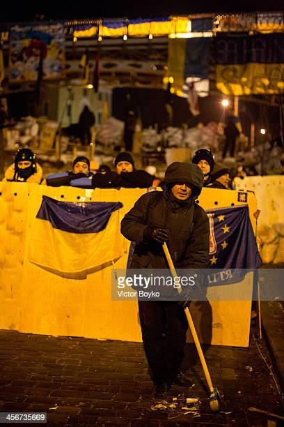 Protester cleans the street near a makeshift barricade near Instytutska street on Maidan Square on December 14 2013 in Kiev Ukraine Antigovernment...