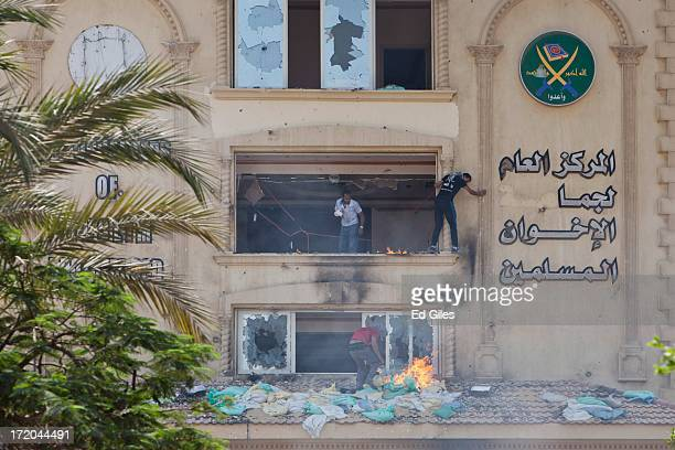 Protester climbs outside a window of the headquarters of Egypt's Muslim Brotherhood as another sets fire to debris as they ransack the building in...