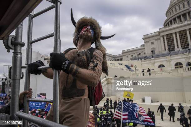 Protester climbs scaffolding as demonstrators swarm the U.S. Capitol building in Washington, D.C., U.S., on Wednesday, Jan. 6, 2021. The U.S. Capitol...