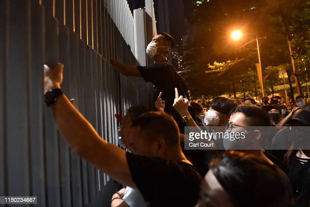 A protester climbs the fence as others shout and gesture outside the Legislative Council building as they demonstrate against the nowsuspended...