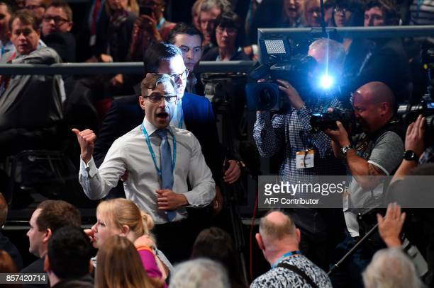 Protester comedian Simon Brodkin gestures as he is escorted out of the auditorium after delivering a piece of paper written as a mock P45 to...