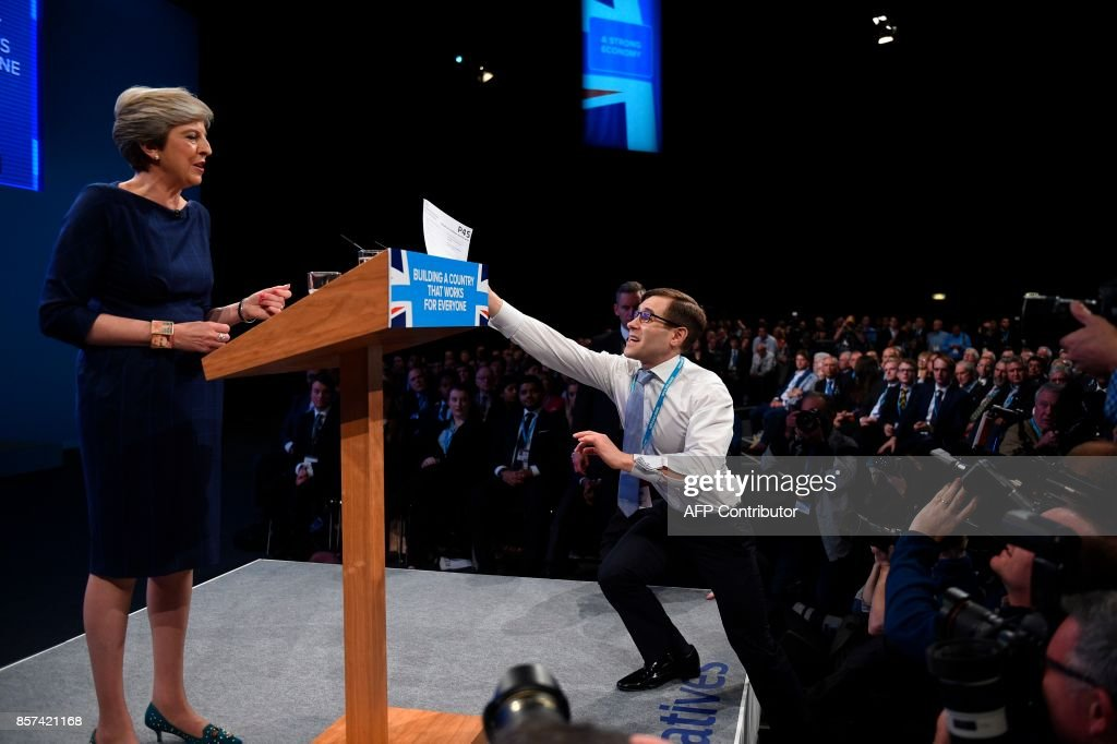 Protester comedian Simon Brodkin (R) gives a piece of paper written as a mock P45 (employee leaving form) to Britain's Prime Minister Theresa May (L) as she was delivering her speech on the final day of the Conservative Party annual conference at the Manchester Central Convention Centre in Manchester, northwest England, on October 4, 2017. The protester interrupted the leader's speech to hand her a paper and then was escorted out of the auditorium. / AFP PHOTO / Oli SCARFF