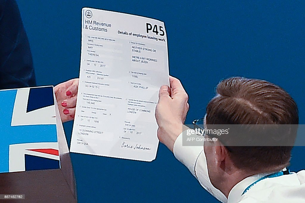 Protester comedian Simon Brodkin (R) gives a piece of paper written as a mock P45 (employee leaving work or unemployment notice form) to Britain's Prime Minister Theresa May as she was delivering her speech on the final day of the Conservative Party annual conference at the Manchester Central Convention Centre in Manchester, northwest England, on October 4, 2017. Comedian Lee Nelson, whose real name is Simon Brodkin, walked up to the stage and gave May the form. /