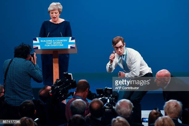 Protester comedian Simon Brodkin gives a thumbsup after he got to the podium and handed a paper with P45 written on it to Britain's Prime Minister...