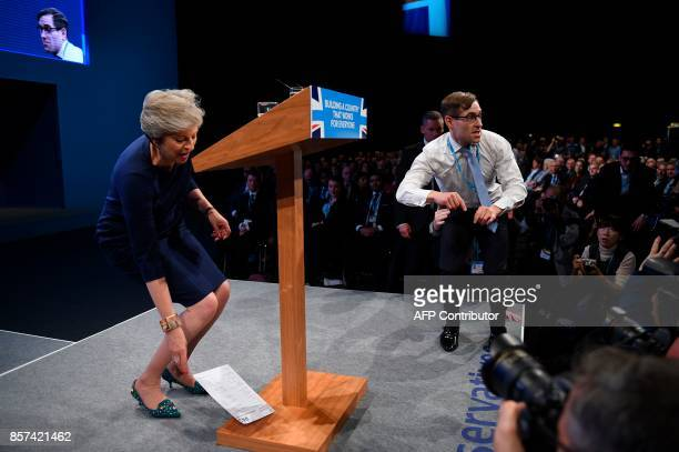 Protester comedian Simon Brodkin leaves the stage aftter delivering a piece of paper written as a mock P45 to Britain's Prime Minister Theresa May...